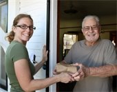 Meals on wheels volunteer delivers a meal to a program participant
