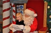 Santa with a child reading a wish list photo.