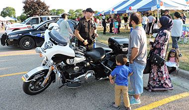 Family looking at police motorcycle with picnic tent in the background