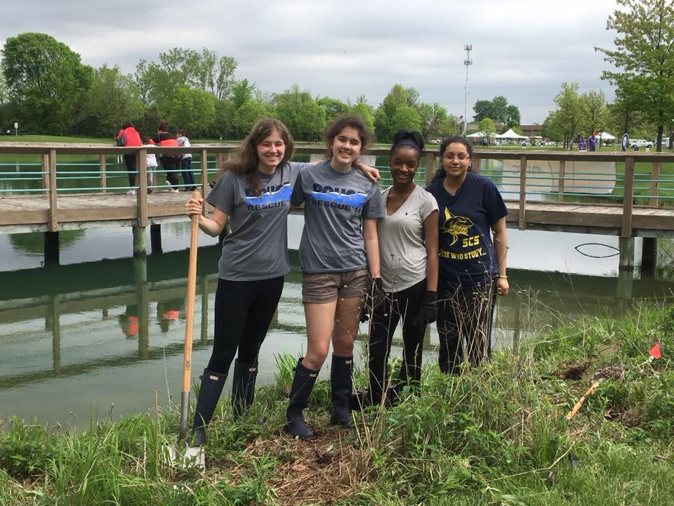 Four volunteers stand next to a pond that they are cleaning up