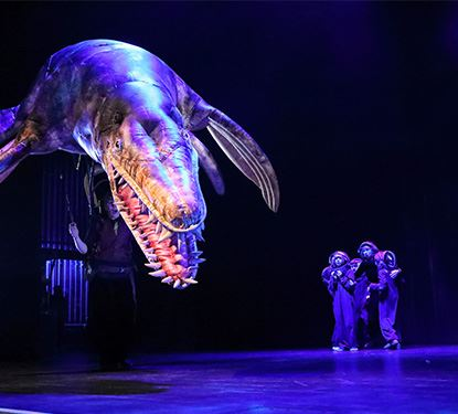 Erths Prehistoric Aquarium Adventure actors onstage with large puppet